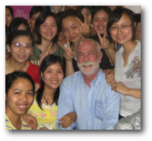 A picture of Bruce Taylor in the midst of international children